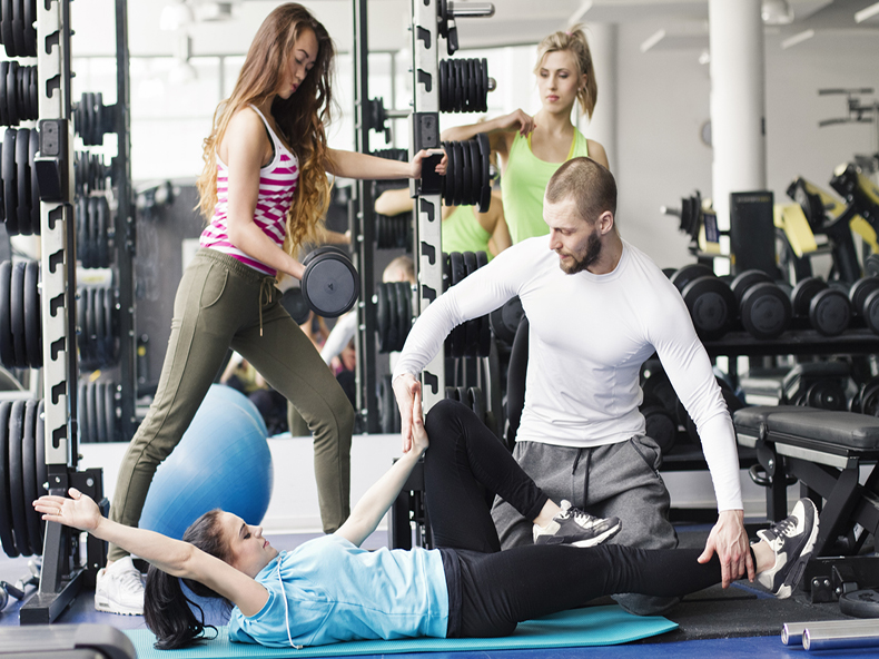 Group of mixed age&race people doing exercises at gym. Sport equipment around in foreground and background (mat, dumbbells, bench, ball, stationary machines). Many roles of people (trainer, exercising people, resting person).